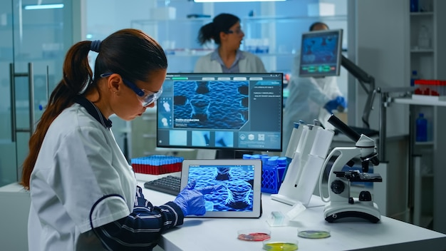 Lab technician doctor analyzing virus evolution looking on digital tablet. team of scientists conducting vaccine development using high tech for researching treatment against covid19 pandemic.