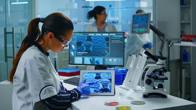 Врач лаборанта анализирует эволюцию вируса смотря цифровую таблетку. команда ученых занимается разработкой вакцины с использованием высоких технологий для исследования лечения пандемии covid19.