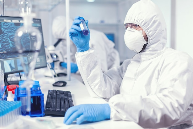 Lab technician dressed in protective suit as safety precaution looking at test tube