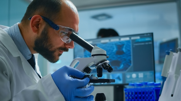 Lab technician examining samples and liquid using microscope in equipped laboratory