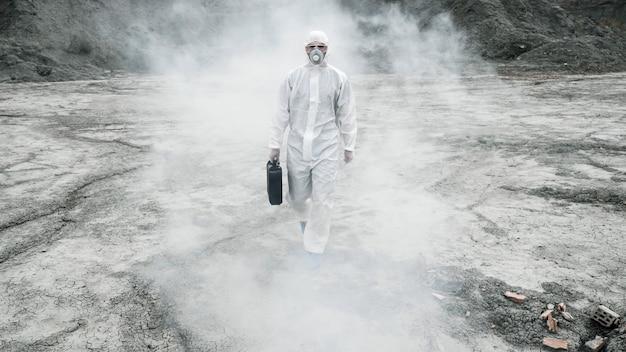 Лаборант в маске и костюме химической защиты идет по сухой земле с ящиком для инструментов до ...
