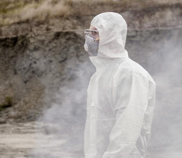 Лаборант в маске и костюме химической защиты идет по сухой земле с ящиком для инструментов сквозь токсичный дым.