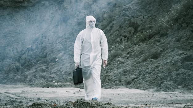 마스크와 화학 보호 복을 입은 실험실 기술자가 도구 상자를 들고 독성 연기를 통해 마른 땅을 걸어갑니다.