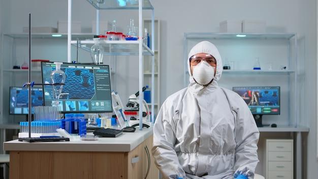 Лаборант в костюме ppe работает с виртуальной реальностью в химической лаборатории. команда биологов изучает эволюцию вакцины с помощью высоких технологий и технологий, исследует лечение против вируса covid19