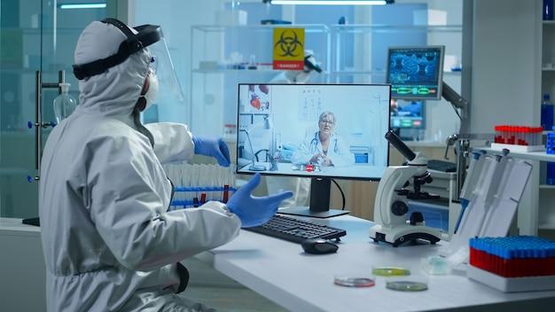 Tecnico di laboratorio in tuta dpi seduto al tavolo nel laboratorio di ricerca medica, tenendo la provetta e parlando in videochiamata con il medico senior che dà consigli online durante la riunione virtuale