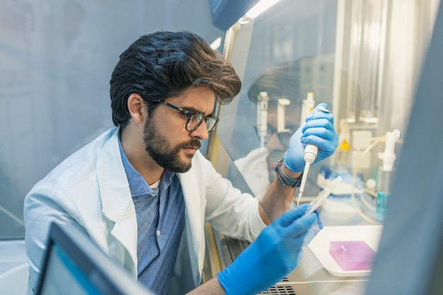 Lab technician working with pipette in molecular laboratory