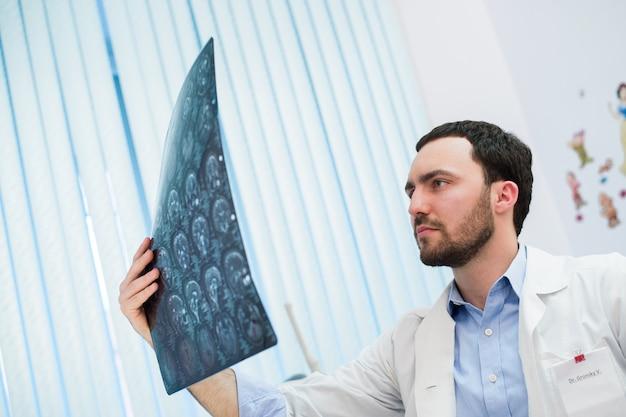 Макрофотография портрет интеллектуального человека медицинского персонала с белым labcoat, глядя на рентгеновское изображение мозга рентгеновского