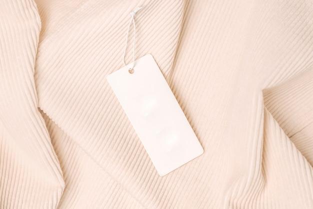 Этикетка и бирка на бежевой вельветовой ткани. макет для дизайна