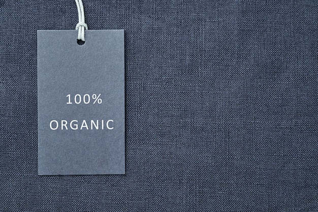 Label on linen fabric background. 100% organic materal