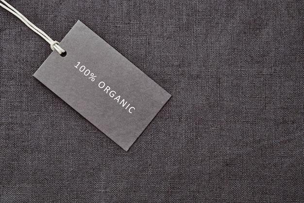 Этикетка на фоне льняной ткани. 100% органический материал
