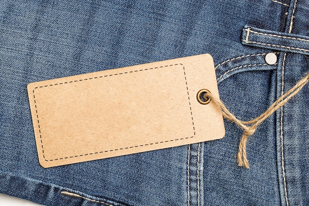 Label price tag mockup on blue jeans from recycled paper.