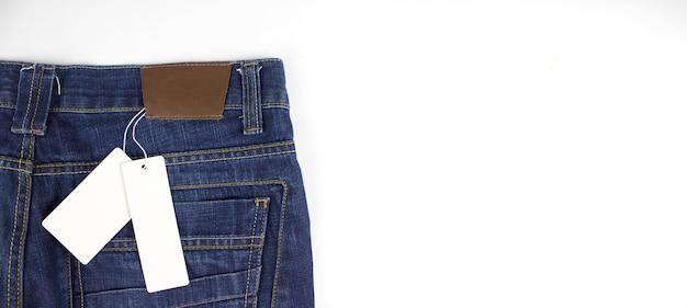 Этикетка макета ценника на синих джинсах. ценник держится на штанах.