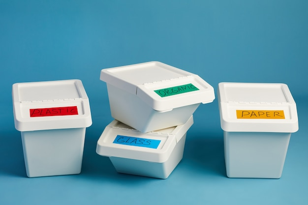 Labeled trash bins for plastic and paper waste in row, sorting and recycling concept