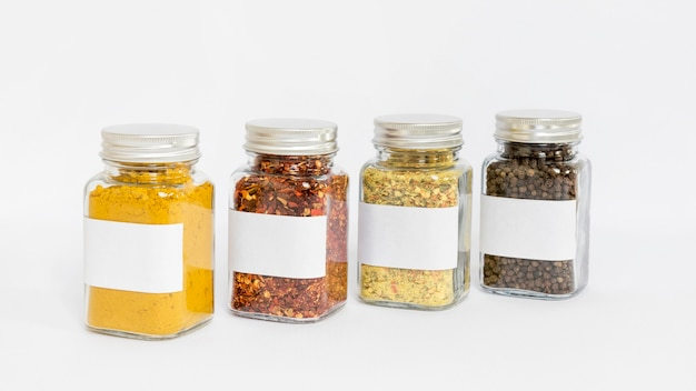 Labelled spices jars on white background