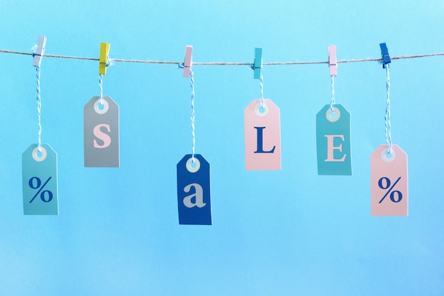 Labels hang on the rope with attached clothespins. they inscription sale.