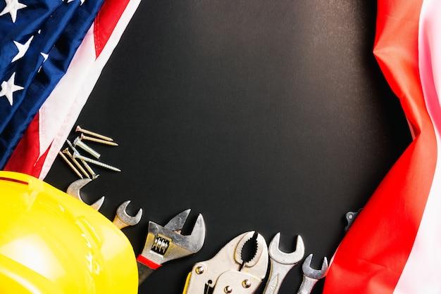 労働者の日の概念上面図黒のアメリカ国旗とさまざまな種類のレンチのフラットレイ