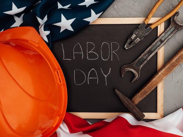 День труда. ручные инструменты и флаг соединенных штатов америки, лежащий на столе. вид сверху, крупный план. поздравления родным, близким, друзьям и коллегам. концепция национального праздника