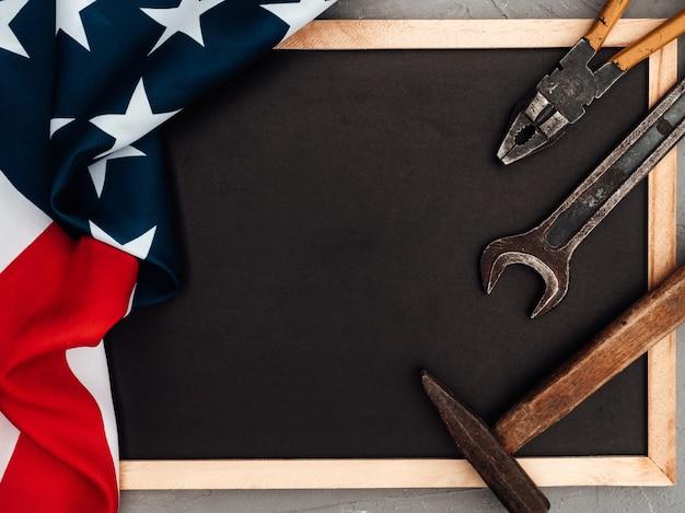 День труда. ручные инструменты и флаг соединенных штатов америки, лежащий на столе