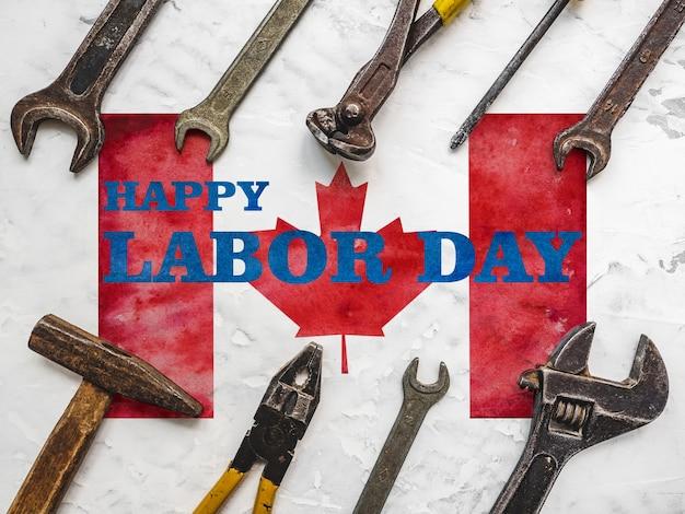 День труда. ручные инструменты, лежащие на фоне канадского флага. вид сверху, крупным планом. готовимся к торжеству. поздравления родным, близким, друзьям и коллегам
