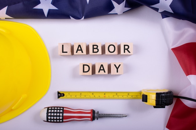 Labor day usa concept, set of various tools,  flag of usa on wooden background with text