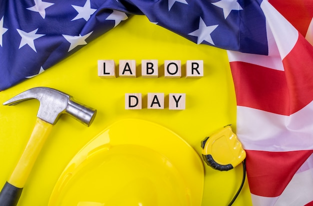Labor day usa concept, set of various tools on yellow paper background with flag of usa.