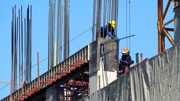 Рабочие работают на строительной площадке и строительной башне из бетона и металлических материалов.