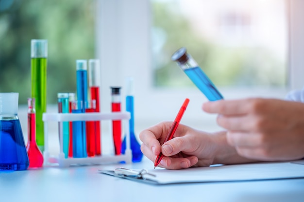 Laboratory assistant conducts clinical laboratory research, holds a blue liquid test tube in his hands and writing the result of the study in clipboard. medicine, pharmacy and cosmetology concept.