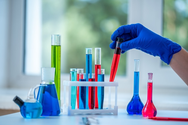 Laboratory assistant conducts clinical laboratory research, holds a red liquid test tube in his hands. medicine, pharmacy and cosmetology concept.