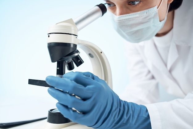 Laboratory assistant wearing a medical mask looking through a microscope professional research