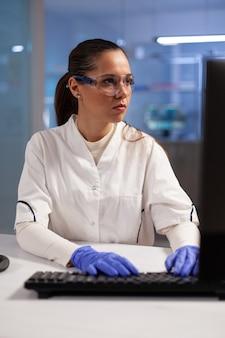 의료 개발 산업에서 테스트 샘플에 컴퓨터를 사용하는 실험실 화학자. 실험실 코트와 장갑을 끼고 미생물학 의료 치료를 하는 백인 과학자 여성.