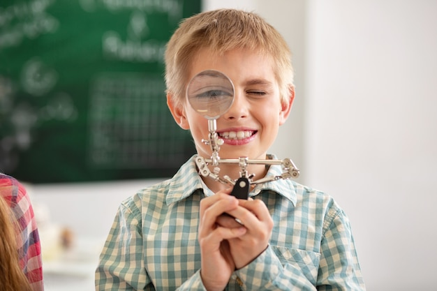 실험실 장비. 학교 실험실에있는 동안 돋보기를보고 쾌활한 좋은 소년