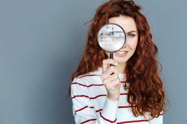 研究所の備品。研究をしている間、陽気なスマートな赤い髪の女性の手にある虫眼鏡のクローズアップ Premium写真