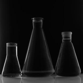 実験装置、黒い背景の上の3つのガラスフラスコ