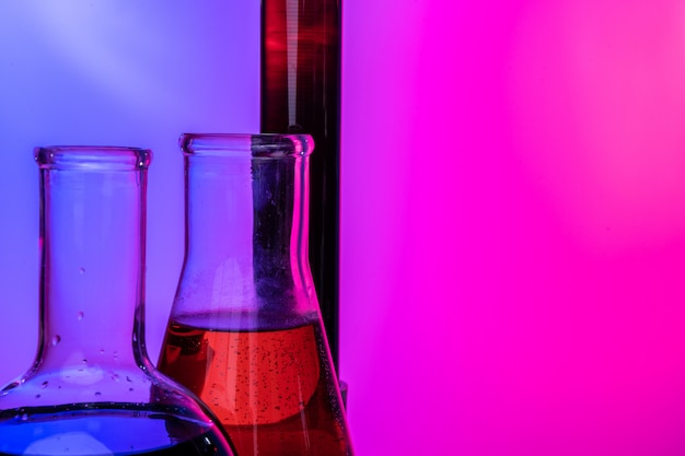 Laboratory glass tubes with chemicals on bright pink