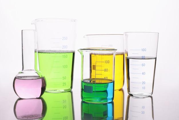 Лабораторная посуда, наполненная разноцветной жидкостью на белом фоне