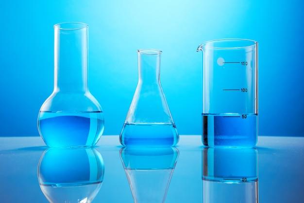Лабораторная посуда с голубой жидкостью на столе на синем фоне. пробирки для экспериментов.
