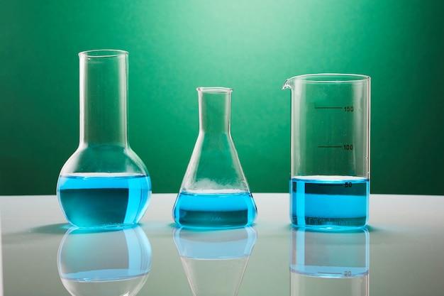 緑の壁に対してテーブルの上に青い液体と実験用ガラス器具。化学分析。実験用の試験管。
