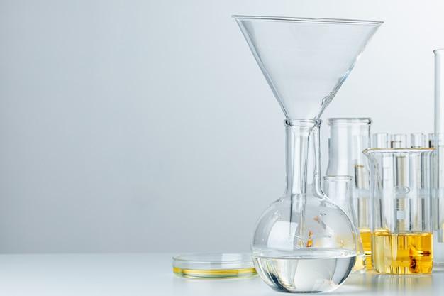 Laboratory glassware with yellow oily liquid on grey background