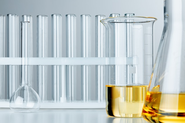 Laboratory glassware with yellow oily liquid on grey background