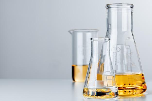 회색 배경에 노란색 유성 액체와 실험실 유리