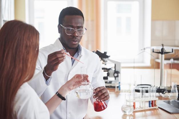 실험실 실험실은 투명한 플라스크의 화학 실험실에서 실험을 수행합니다. 출력 공식.