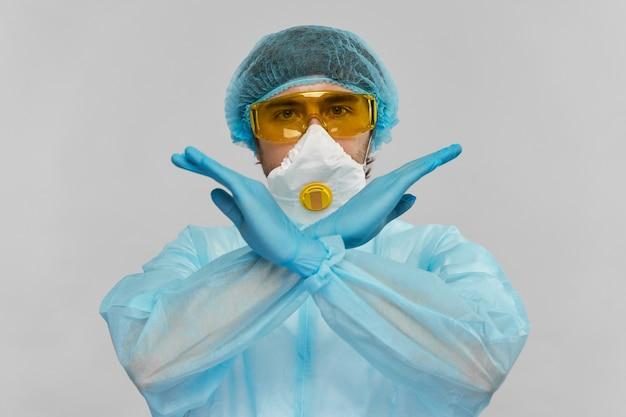 灰色で隔離されたカメラに停止ジェスチャーを示すバイオハザード衣装の実験室の医学者