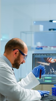 Laboratory medical stuff disscussing about vaccine development holding test tube with blood sample. medical scientist working with dna scan image in modern equipped laboratory using high tech