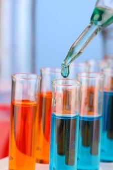 유리 테스트 튜브 위에 색 액체 방울이있는 실험실 피펫을 닫습니다.