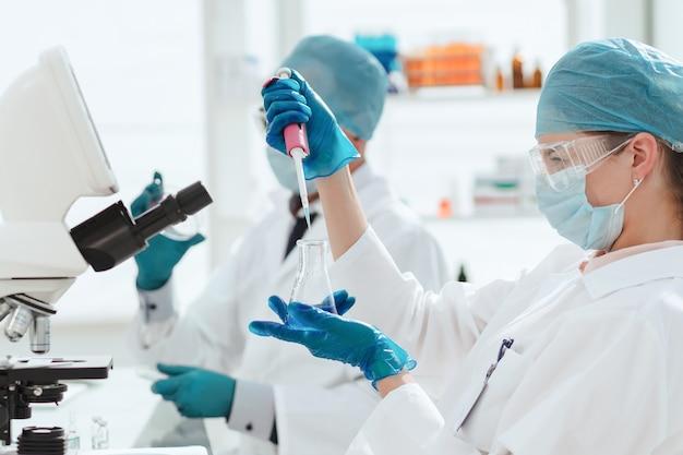 Сотрудники лаборатории тестируют новую вакцину. наука и здоровье.