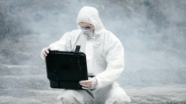 A laboratory technician in a mask and a chemical protective suit opens a toolbox on dry land, around toxic smoke.