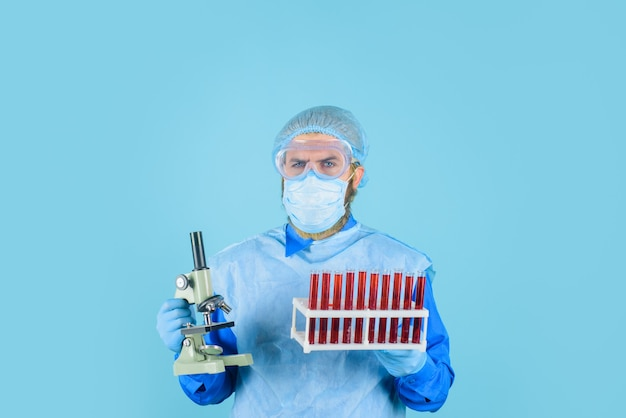 Laboratory technician with blood test tubes and microscope doctor analyzing blood sample in clinic