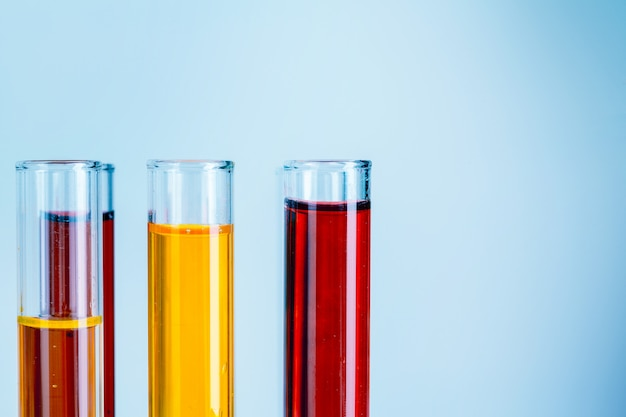 Laboratory test tubes with red and yellow liquids on light blue background