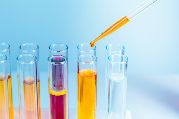 Laboratory test tubes with red and yellow liquids on light blue