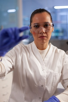 Laboratory worker analyzing blood sample on glass